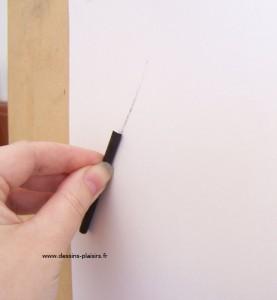 photo de ma main tenant un fusain contre une feuille de papier